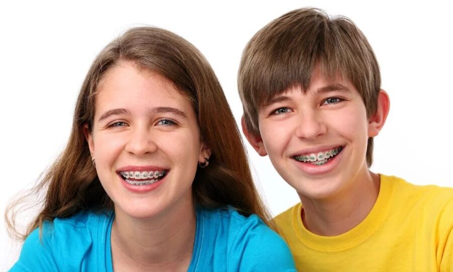 Teen siblings with braces smiling