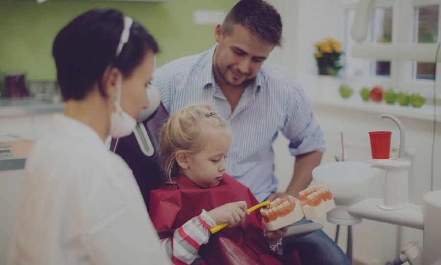Dentist and dental assistant teaching a young patient proper brushing