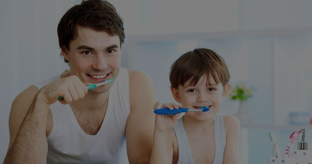 Father and son smiling and brushing teeth together